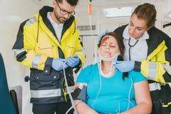 Mediziner, die um abgehärteter Frau im Krankenwagen sich kümmern Stockfotografie
