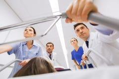Mediziner mit Frau auf Krankenhausrollbahre am Notfall stockbilder