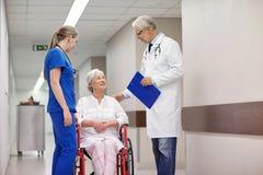 Mediziner und ältere Frau im Rollstuhl am Krankenhaus Stockfotos