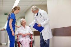 Mediziner und ältere Frau im Rollstuhl am Krankenhaus Lizenzfreie Stockbilder