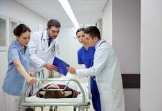 Mediziner und Patient auf Krankenhausrollbahre am Notfall stockfotografie