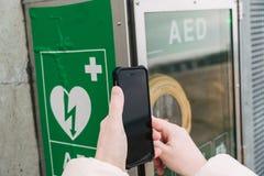 Medizinherz-lungen-wiederbelebungs-Notruf Die kaukasische Frau benutzt Telefon 911 nennend Hilfe Gerätkasten-AED automatisch lizenzfreie stockfotografie