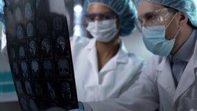 Medizinische Arbeitskräfte, die das menschliche Gehirn MRI, Ergebnis besprechend, um Diagnose einzustellen betrachten lizenzfreie stockbilder