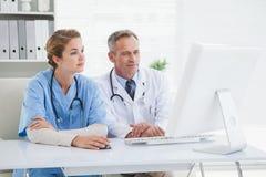 Medizinische Arbeitskräfte, die einen Computer betrachten Stockbild