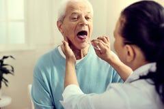 Medizinische Arbeitskraft, die Mandeln des älteren Herrn überprüft lizenzfreie stockbilder