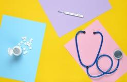 Medizinische Ausrüstung auf einem Hintergrund des farbigen Papiers Stethoskop, Thermometer, Flasche Vitamine MEDIZINISCHES Konzep lizenzfreies stockfoto