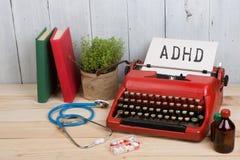 medizinische Diagnose - Doktorarbeitsplatz mit Stethoskop, Pillen, Schreibmaschine mit Text ADHD Aufmerksamkeitsdefizit-Hyperakti stockbild