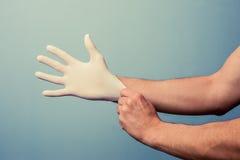 Medizinische Fachkraft, die auf chirurgische Handschuhe sich setzt Stockfotografie