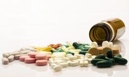 Medizinische Flasche und bunte Pillen über Weiß lizenzfreies stockbild
