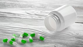 Medizinische grüne Pillen und weiße Flasche auf hölzernem Hintergrund Stockbilder