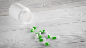 Medizinische grüne Pillen und weiße Flasche auf hölzernem Hintergrund Stockfoto
