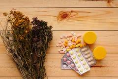 Medizinische Kräuter und Tabletten auf dem Tisch Lizenzfreies Stockbild