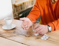 Medizinische Pille auf der runzligen Hand eines alten Mannes Lizenzfreies Stockbild