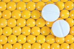 Medizinische Pillen auf gelbem Pillehintergrund Stockfotografie