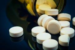 Medizinische Pillen aus ihrer Flasche heraus Lizenzfreie Stockbilder