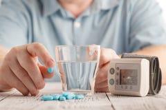 Medizinische Pillen gegen Bluthochdruck in der Hand, Ausrüstung für messenden Blutdruck lizenzfreie stockfotos