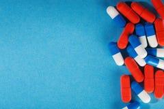Medizinische Pillen weiß-blau und rot auf einem hellen Hintergrund Stockfoto