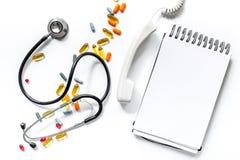 Medizinische Sachen mit Notizbuch auf weißer Draufsichtzusammensetzung des Hintergrundes mit phonendoscope und Pillenanrufdoktors lizenzfreies stockfoto