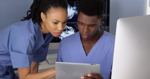 Medizinische Spezialisten des Afroamerikaners, die Computer und Tablette verwenden Stockfotos