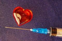 Medizinische Spritze nahe dem Glasherzen Stockbilder