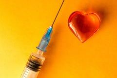 Medizinische Spritze und Glasein herz, das auf farbigem Papier des Grüns, Herz liegt Stockfotos