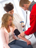 Medizinische Unterstützung - messender Blutdruck Stockfotografie