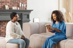 Medizinischer Begleiter, der im Wohnzimmer und im Ablesenbuch für Patienten sitzt lizenzfreie stockfotografie