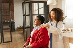 Medizinischer Begleiter, der irgendeine Massage für Frau nach Chirurgie macht lizenzfreie stockfotos