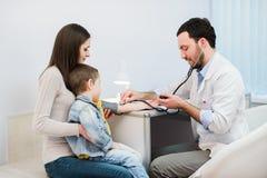 Medizinischer Besuch des kleinen Jungen - behandeln Sie messenden Blutdruck eines Kindes Stockbild