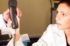 Medizinischer Sekretär, der dem Doktor ein Telefon übergibt Stockbild