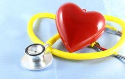 Medizinischer Stethoskopkopf und rote das Spielzeugherz, die auf Kardiogramm liegt, entwerfen Nahaufnahme Hilfe, Prophylaxe, Kran Stockfotografie