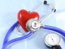 Medizinischer Stethoskopkopf und rote das Spielzeugherz, die auf Kardiogramm liegt, entwerfen Nahaufnahme Hilfe, Prophylaxe, Kran Stockfoto