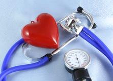 Medizinischer Stethoskopkopf und rote das Spielzeugherz, die auf Kardiogramm liegt, entwerfen Nahaufnahme Hilfe, Prophylaxe, Kran Lizenzfreie Stockfotos