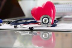 Medizinischer Stethoskopkopf und rotes Spielzeugherz, die auf Kardiogramm c liegt Stockfoto