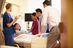 Medizinischer Team Meeting Around Female Patient im Krankenhauszimmer Stockfotos