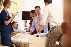 Medizinischer Team Meeting Around Female Patient im Krankenhauszimmer Lizenzfreie Stockfotos