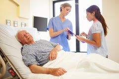 Medizinischer Team Meeting As Senior Man schläft im Krankenhauszimmer Lizenzfreie Stockfotos