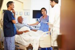Medizinischer Team Meeting With Senior Man im Krankenhauszimmer Stockfoto