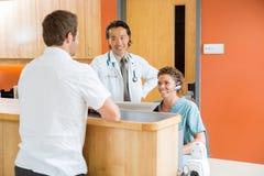 Medizinischer Team With Patient At Receptions-Schreibtisch Stockbild