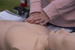 Medizinischer Trainer teilt CPR-Techniken mit einer Attrappe stockfotos