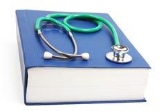 Grünes Stethoskop, das auf einem starken blauen Buch liegt Stockfotos