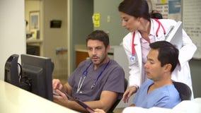 Medizinisches Personal, das an der beschäftigten Krankenschwester-Station arbeitet stock video