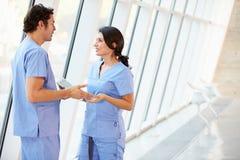 Medizinisches Personal, das im Krankenhaus-Korridor mit Digital-Tablette spricht Stockbilder