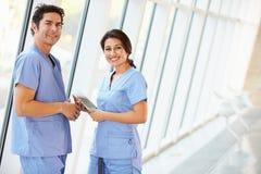 Medizinisches Personal, das im Krankenhaus-Korridor mit Digital-Tablette spricht Stockfotos