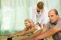 Medizinisches Personal mit älteren Leuten an der Turnhalle Stockbilder