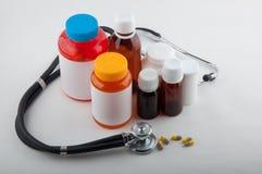 Medizinisches phonendoscope, Pillen und bunte Flaschen Stockbilder