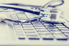 Medizinisches Stethoskop auf Computertastatur lizenzfreie stockfotos