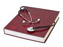Medizinisches Stethoskop auf dem roten Buch. Lizenzfreies Stockfoto