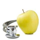 Medizinisches Stethoskop mit dem grünen Apfel lokalisiert auf weißem Hintergrund Konzept für Diät, Gesundheitswesen, Nahrung oder Stockbild