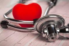 Medizinisches Stethoskop mit Kardiogramm- und Rotherzen Lizenzfreies Stockbild